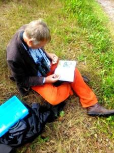 Herman met het boek erbij, bezig met determineren